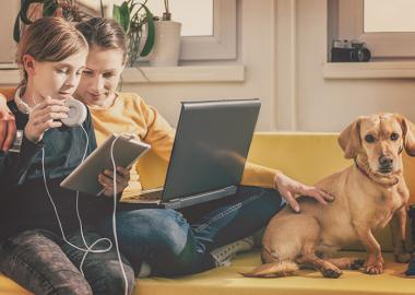 children sitting on couch with their dog